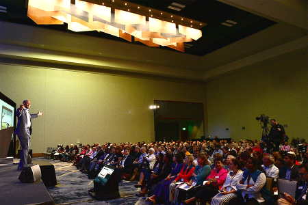 Toastmasters International Call for Presenters - Speaker on stage speaking to a crowd of people