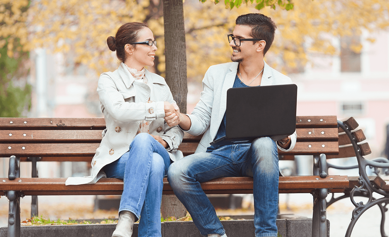 Woman and man with laptop on park bench shaking hands