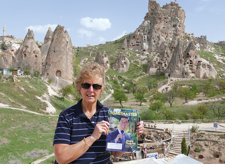 Virginia A. Malik, ACB, from Linden, New Jersey, poses near a village of rock houses in Uchisar, Cappadocia, Turkey.