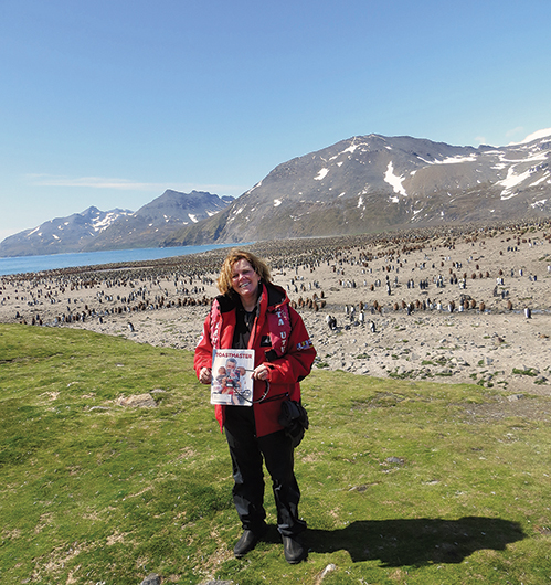 France Castonguay, from Montreal,  Canada, poses with penguins in South Georgia  Island, UK, near the Antarctic Peninsula.