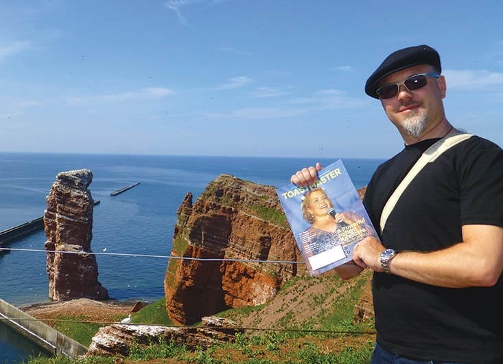 Marcus Gadient, from Basel, Switzerland, visits Helgoland, Germany, to see the rock formation, Lange Anna, pictured in the background.