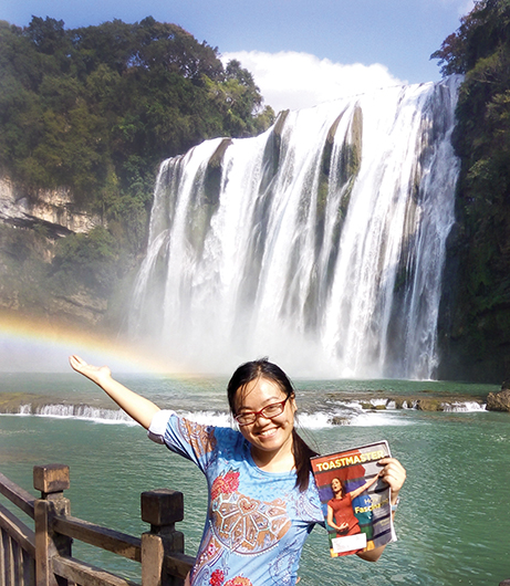 Aurore Liang, ACB, CL, from Montreal, Quebec, Canada, stands in front of the Huangguoshu Waterfall in China.