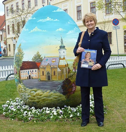 Vesna Kavaz, from Athabasca, Alberta, Canada, stands in front of a hand-painted Easter egg on display in Zagreb, Croatia.