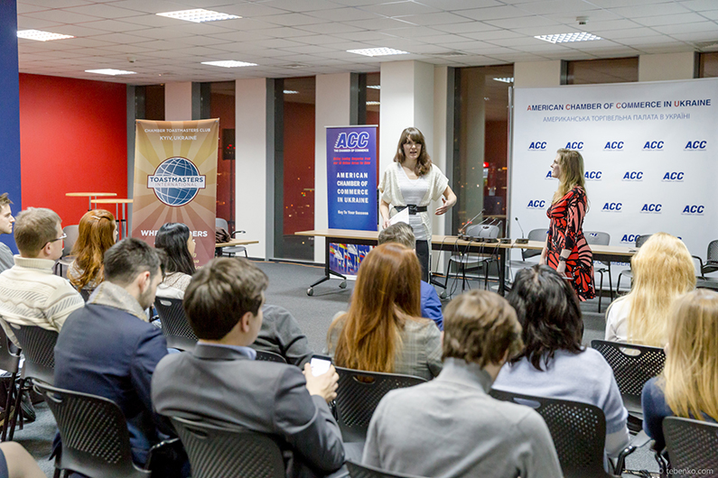 Guests of the Chamber Toastmasters club open house in Kiev, Ukraine, raise their hands to speak during a round of Table Topics.
