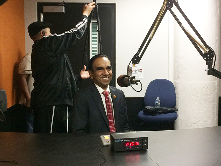 International President Balraj Arunasalam, prepares for a broadcast for iHeartRadio.
