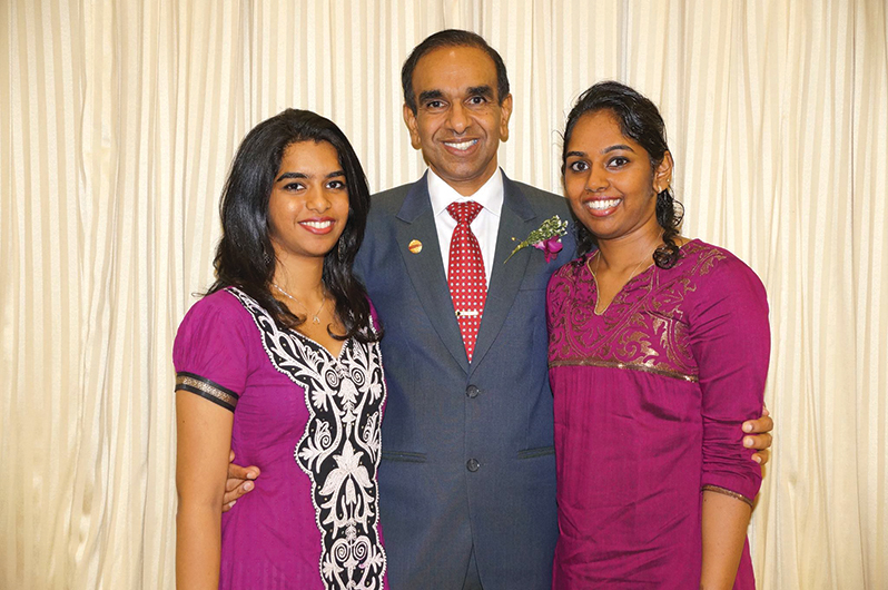 The proud father stands with daughters Mahishaa (left) and Avisha (right).