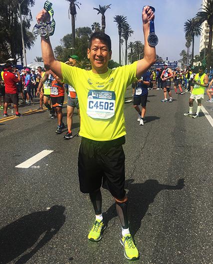Yu celebrates finishing the LA Marathon in Los Angeles, California in March 2017.