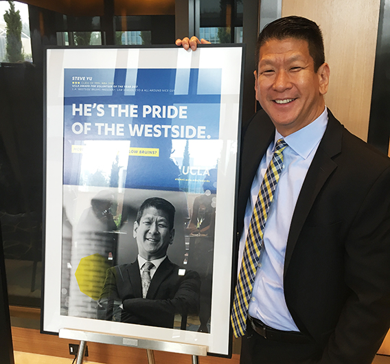A well-liked teacher and mentor in the UCLA community, Yu poses next to a poster of himself after being recognized with the UCLA Alumni Volunteer of the Year Award.