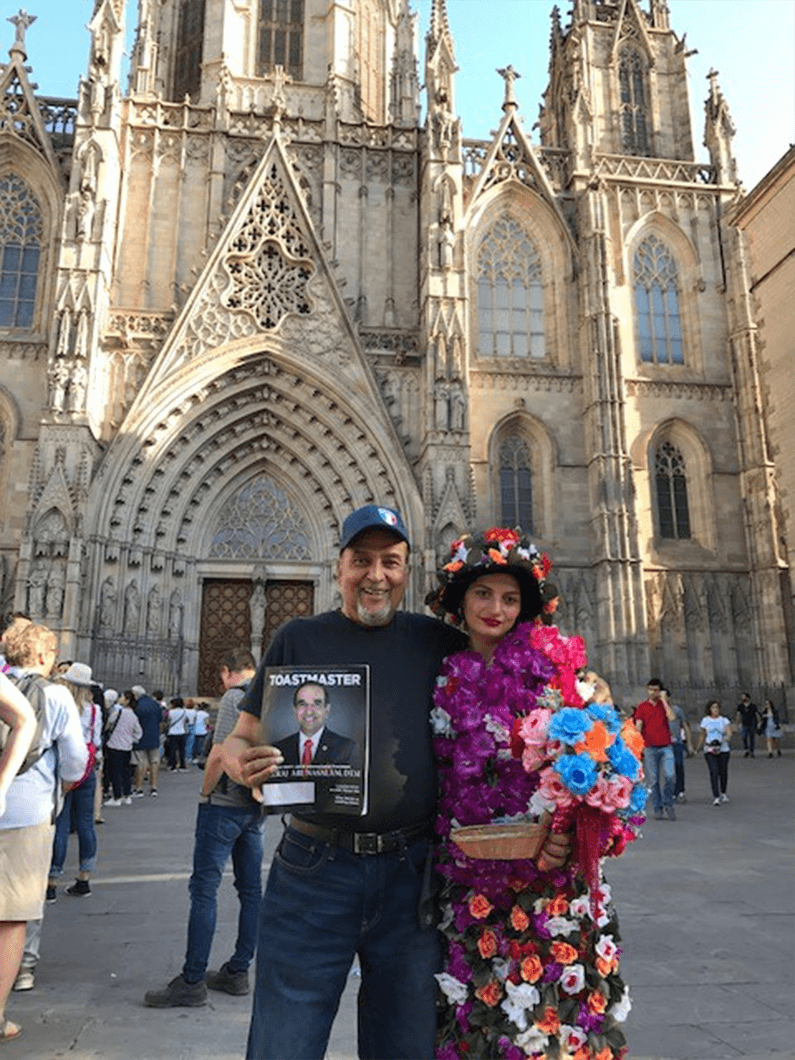 Azad Hamid, ACG, ALB, of Toronto, Canada, with a local flower vendor outside the Cathedral of the Holy Cross and Saint Eulalia, in Barcelona, Spain.