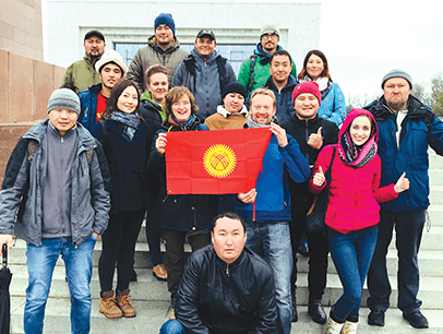 Instructors from the tour-guide training company EastguidesWest with a group of tourism students holding the flag of Kyrgyzstan in the capital city of Bishkek. Photo by EastguidesWest