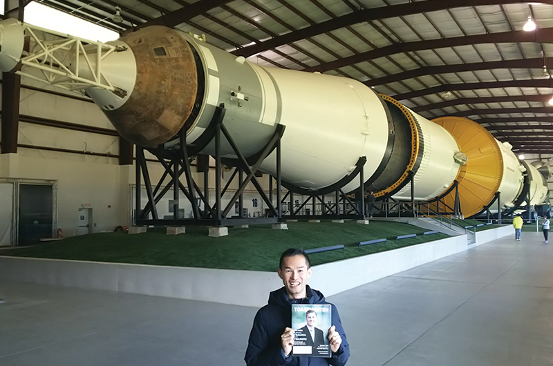Yoshiyuki Kajikawa, ACB, ALB, from Nishinomiya-Shi Hyogo-Ken, Japan, poses near the Saturn V rocket at NASA Johnson Space Center in Houston, Texas.