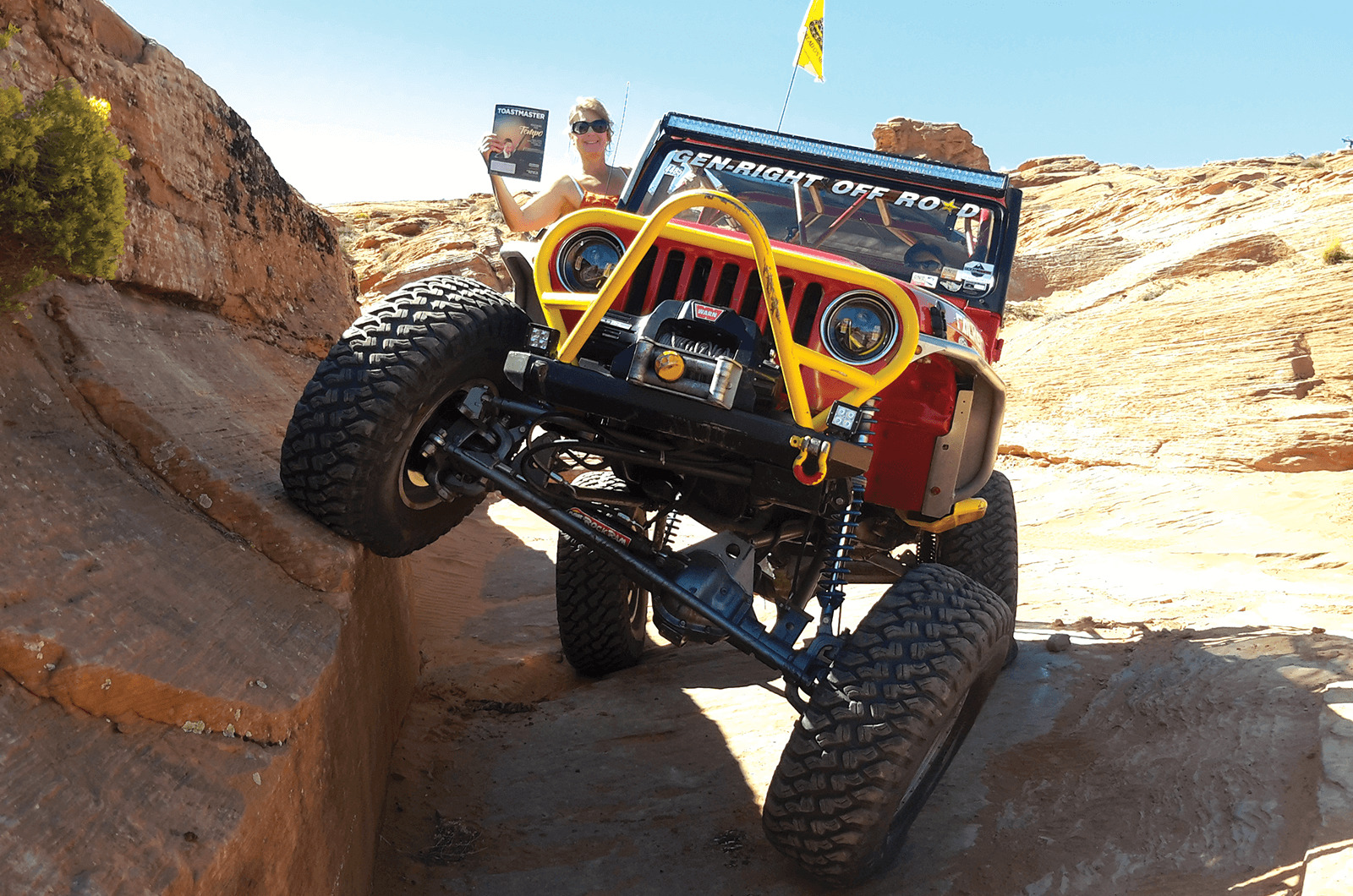 Marisa whittington, ACS, ALB, of Draper, Utah, hangs out of her off-road Jeep in the desert.
