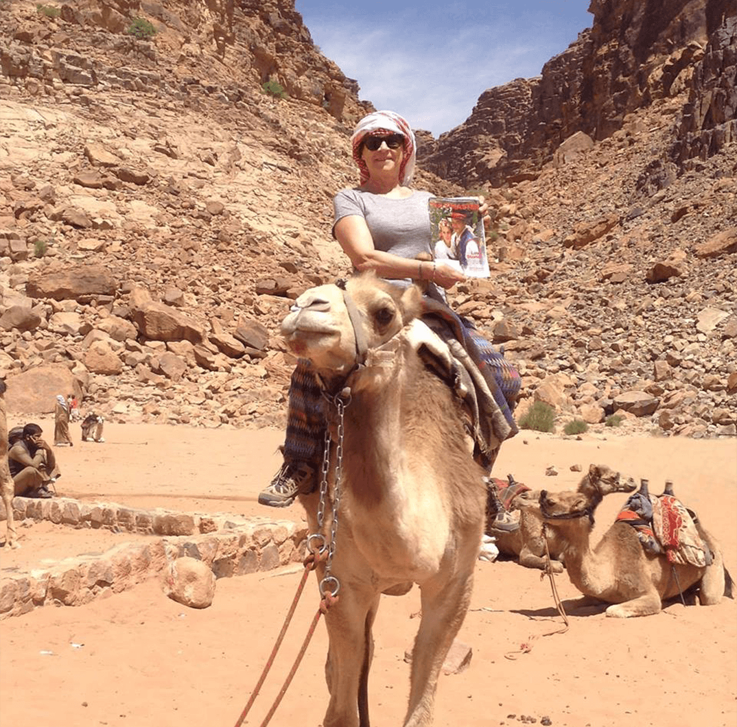 Martine Gouardo Marsat of Brussels, Belgium, enjoys a camel ride in the Wadi Rum desert, Jordan.