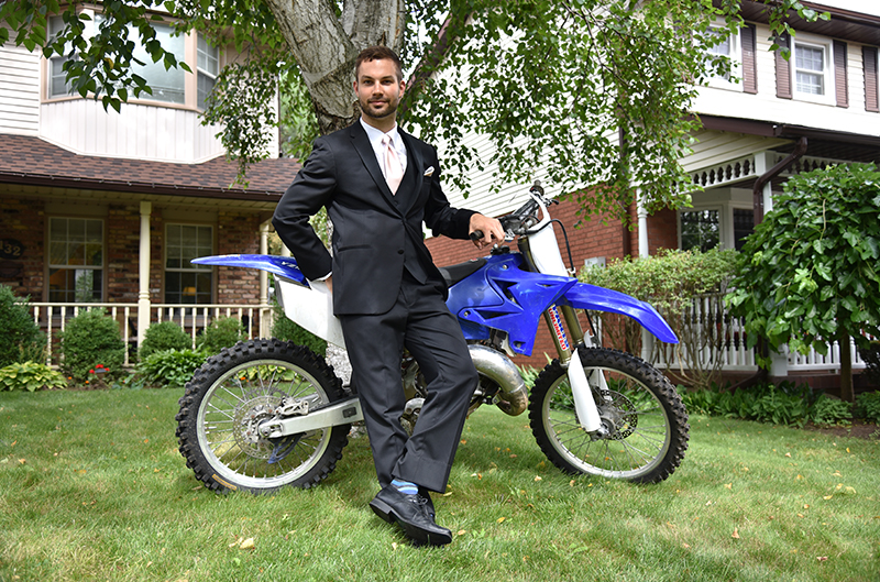 Myles, who grew up racing motocross in the U.S. and Canada, poses with his bike.