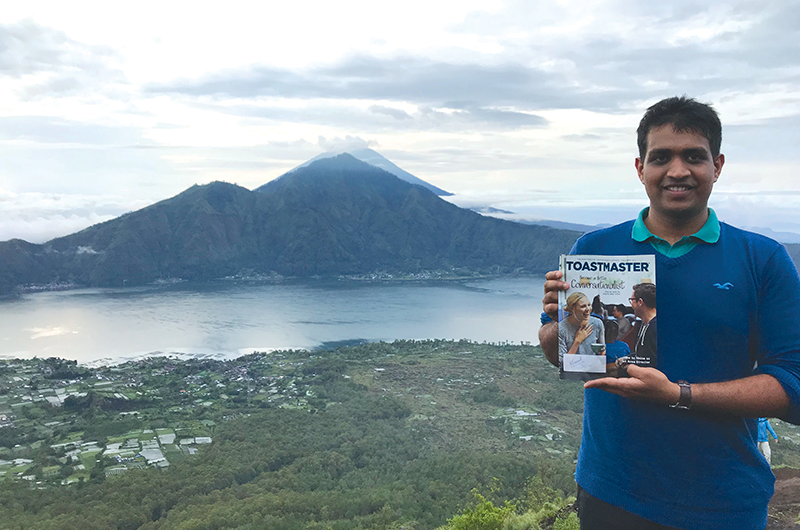Siddharth Vedulla, CL, from Hyderabad, India, poses after trekking Mount Batur in Bali, Indonesia, with Mount Agung in the background.