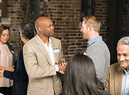 Two men shaking hands at a Toastmasters Open House