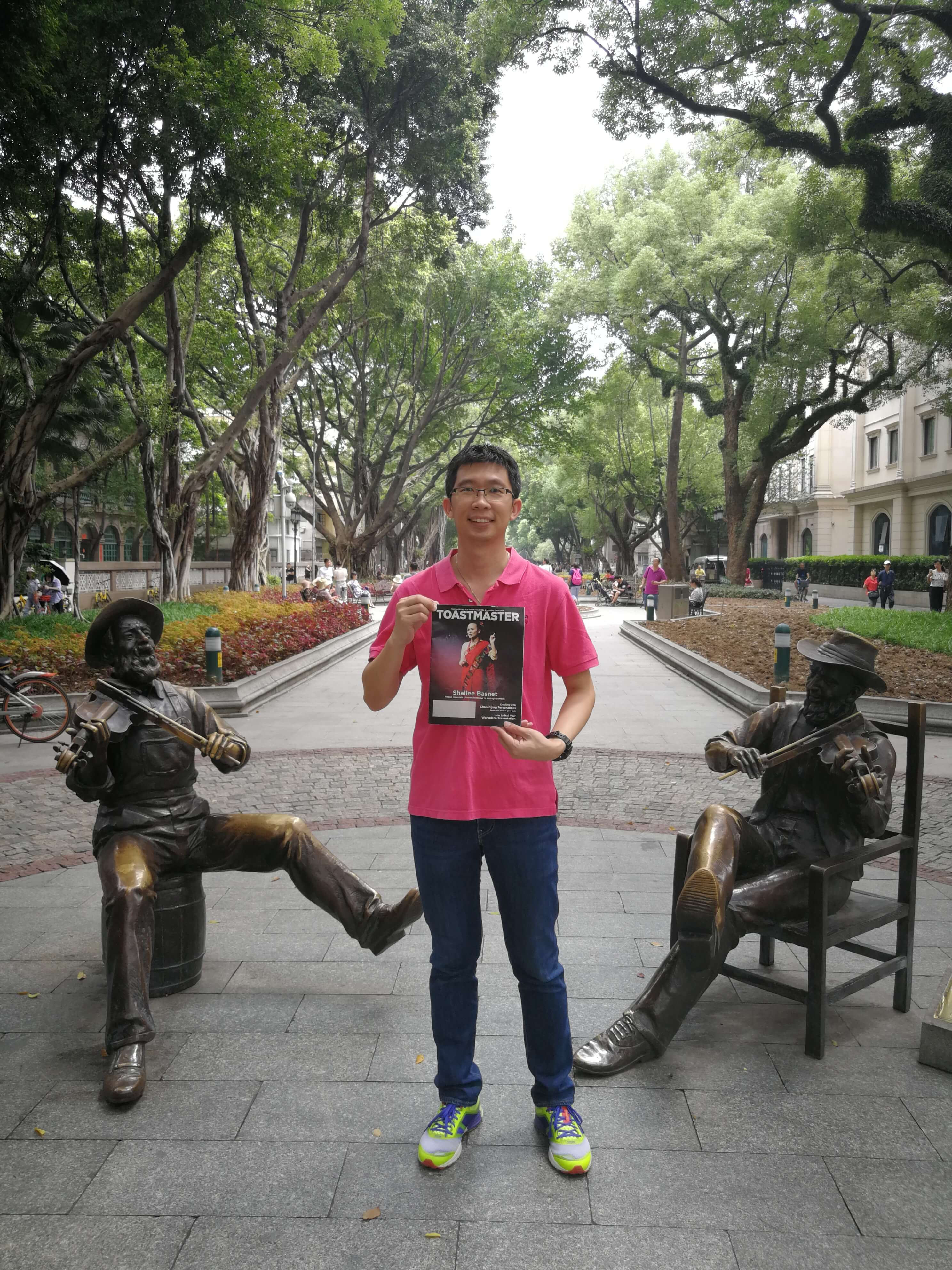 Goh Chee Yong of Petaling Jaya, Malaysia, stands between two violinist statues in Shamian Park, a sandbank island in Guangzhou, China.