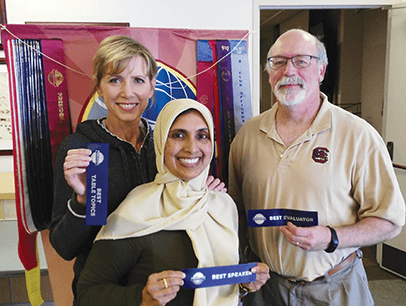 Heidi Swan, Bilquis Ahmed and Ron Maroko pose with Toastmasters ribbons