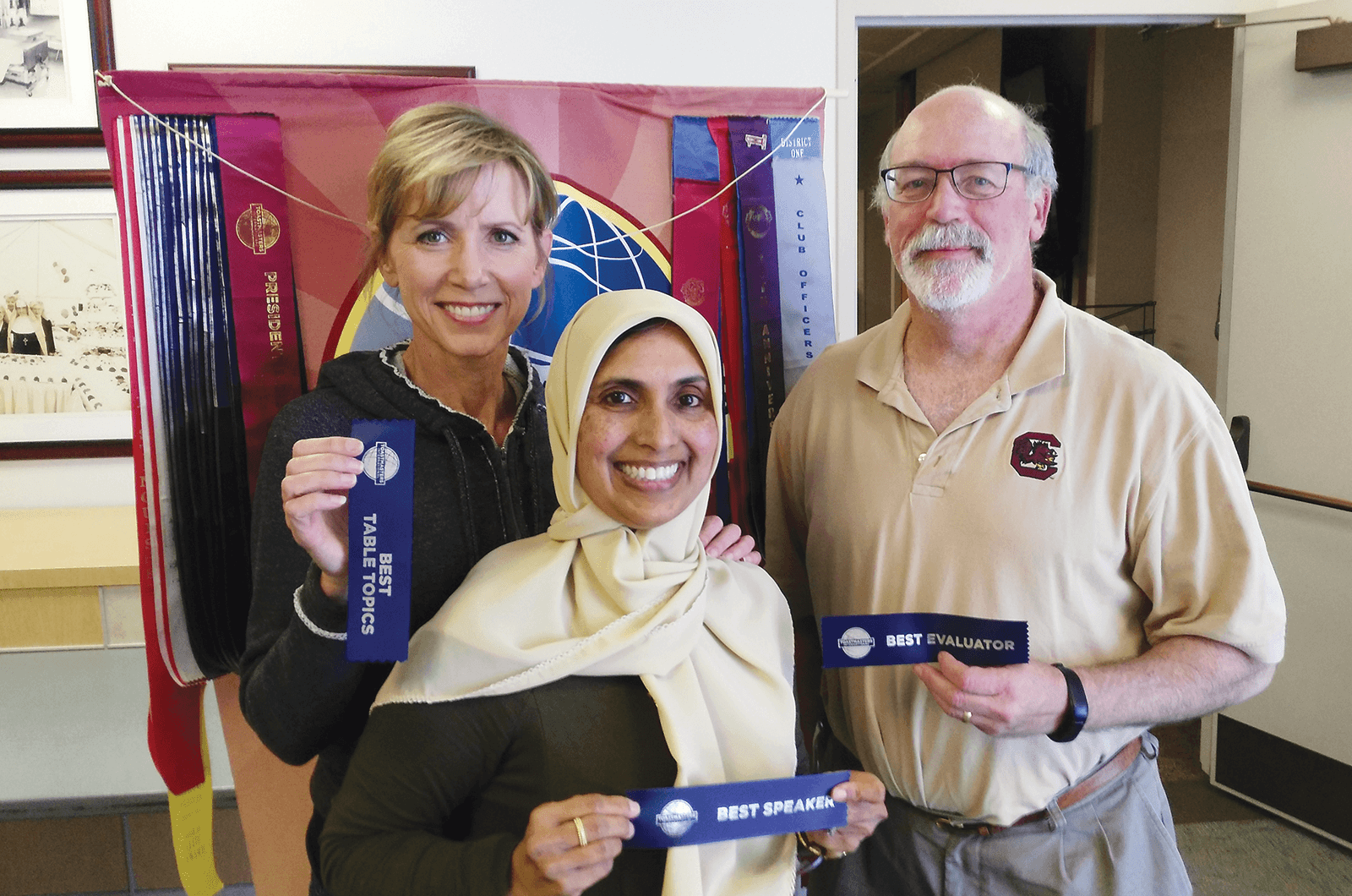 Heidi Swan, Bilquis Ahmed and Ron Maroko pose with Toastmasters ribbons at a Torrance Chamber of Commerce club meeting in California.