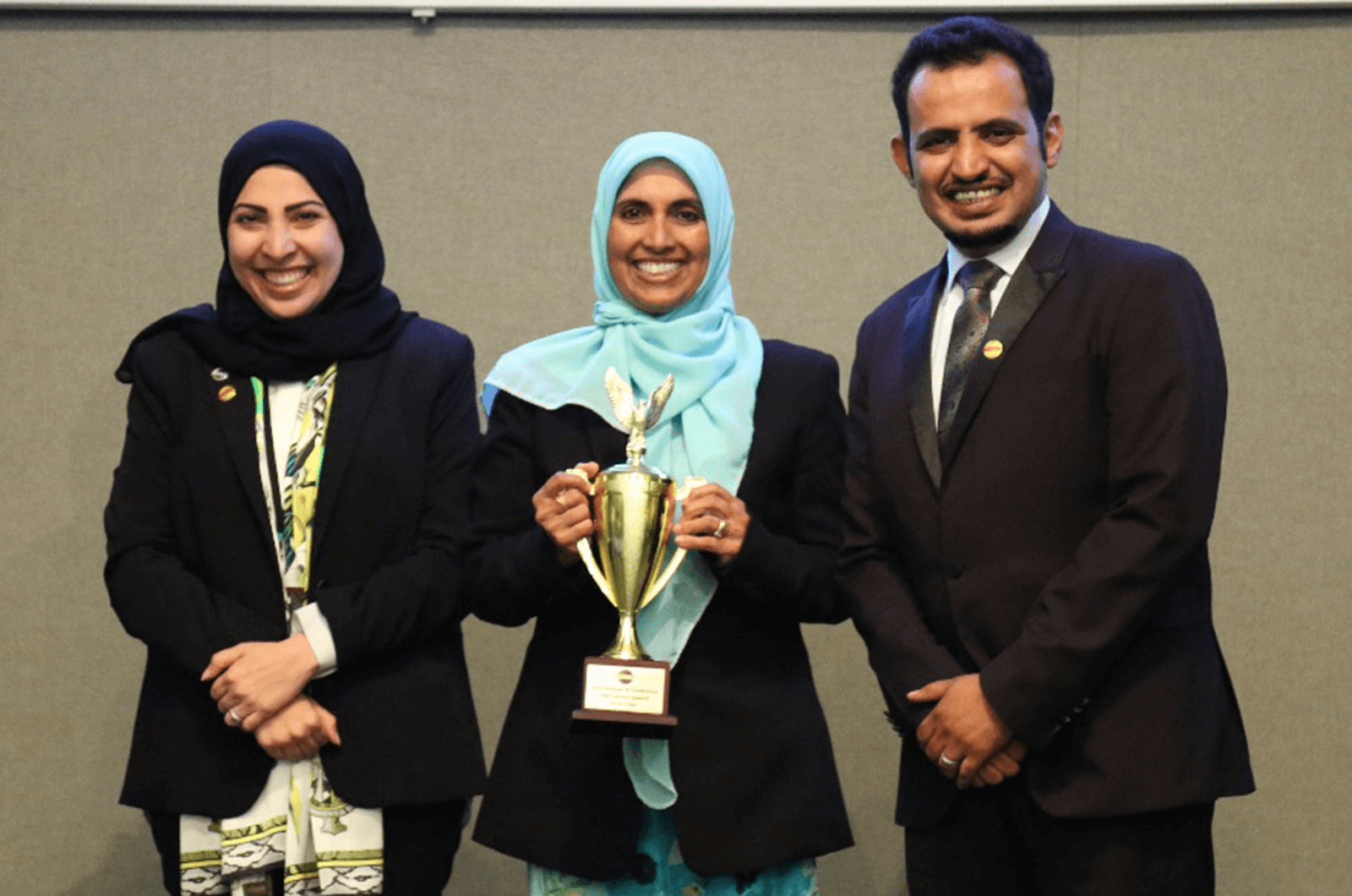 Bilquis proudly holds up a trophy while standing next to 2015 World Champion of Public Speaking Mohammed Qahtani in Saudi Arabia in 2018.