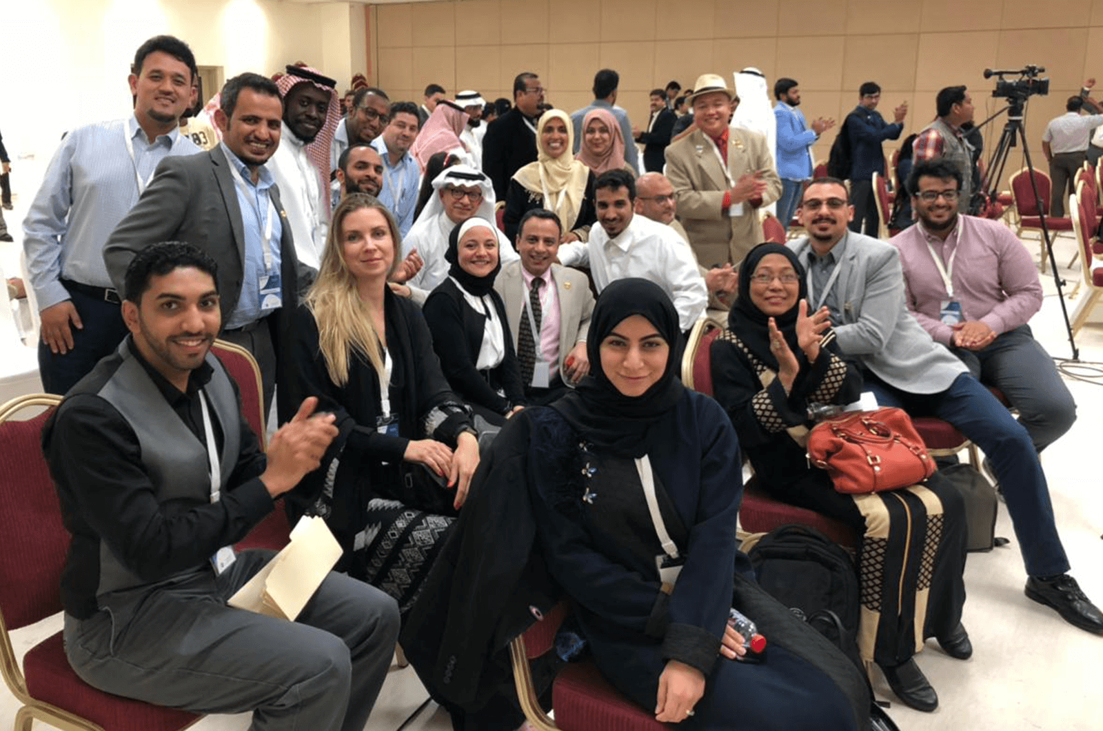 Bilquis Ahmed (pictured in back wearing yellow hijab), poses with her fellow Toastmasters in Saudi Arabia.