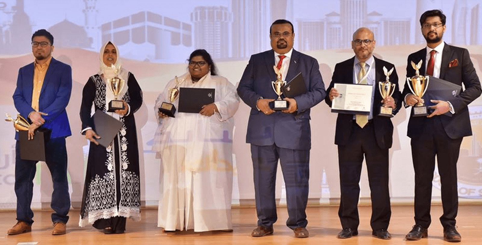 Bilquis (second from left) holds her trophy onstage after winning at the District 79 speech contest in 2018.