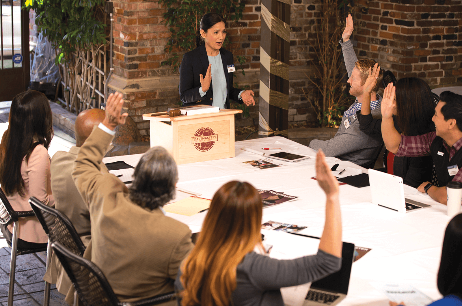 Female standing at Toastmasters lectern while members raise their hands