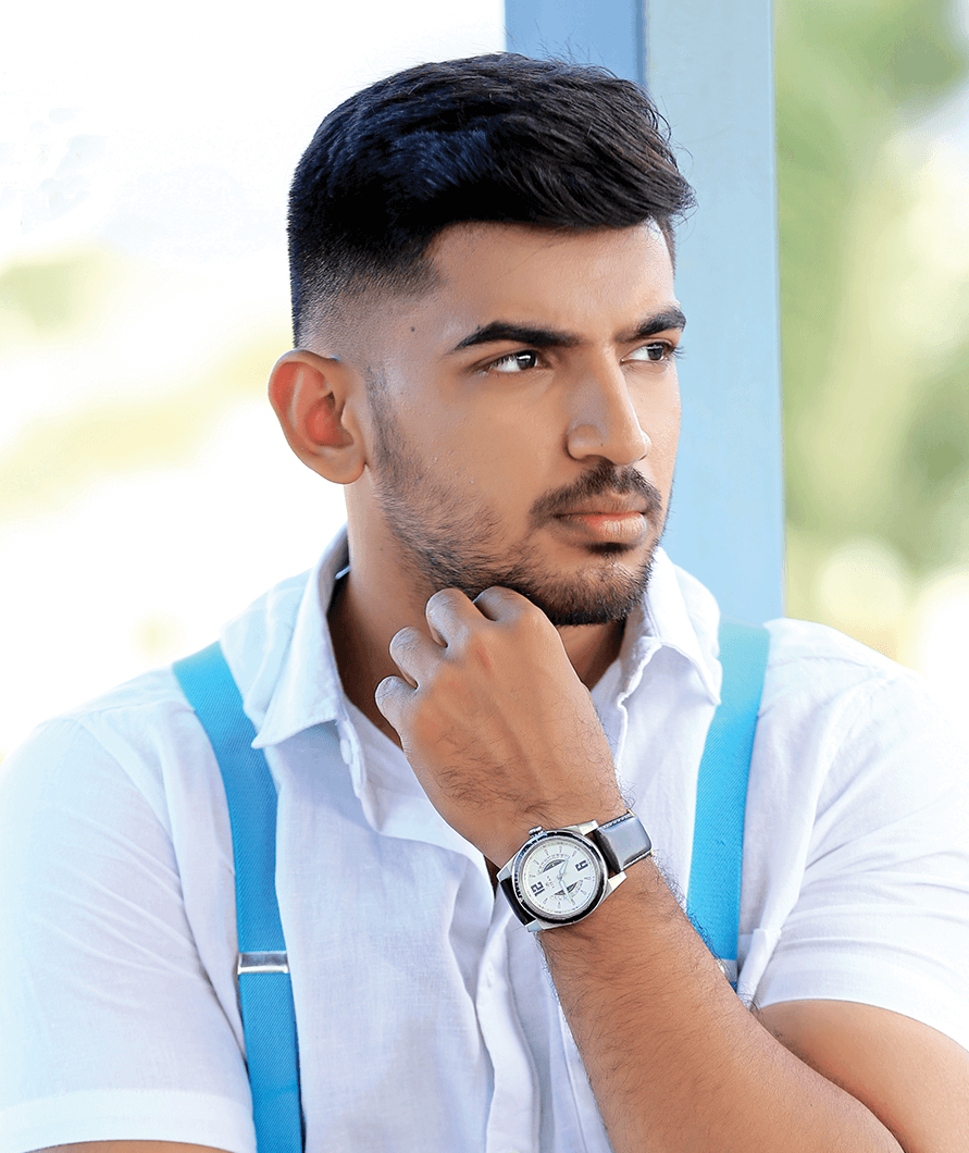 Abishek P in white shirt and blue suspenders poses