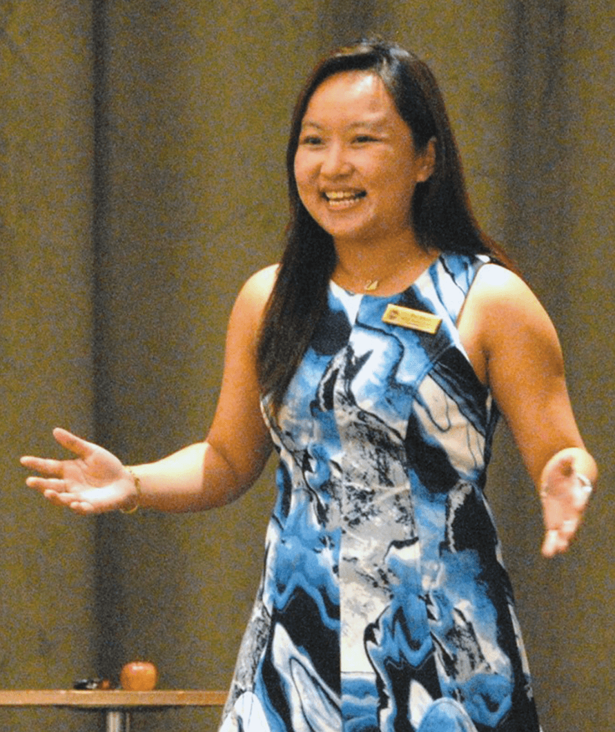 Jessica Chai Pei Shan gestures onstage while giving a speech