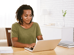 Woman in green shirt on laptop