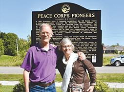 Daniel Grundtner in purple shirt with Ruth Alliband in white scarf in front of Peace Corp sign
