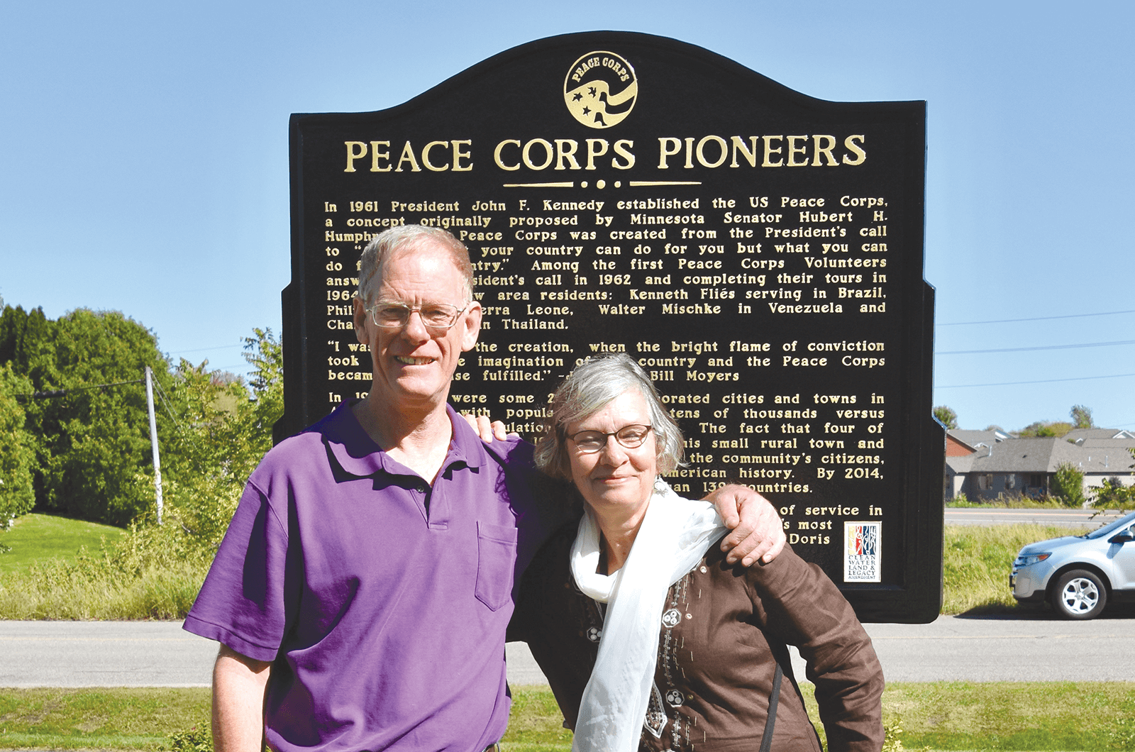 Daniel Grundtner and Ruth Alliband stand in front of a Peace Corp sign in Minnesota.