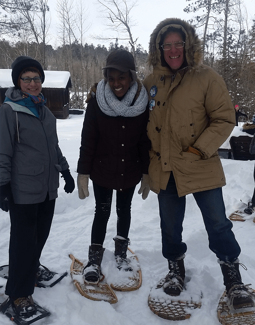 Minnesota Returned Peace Corps Volunteers Toastmasters Amy Earle, Phoebe Munene and Dan Grundtner pose outdoors in snowshoes on a club outing. Munene joined MRPCV as an agriculture student at the University of Minnesota.