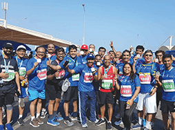 Members of Khimji Toastmasters in blue shirts pose after running Muscat Marathon