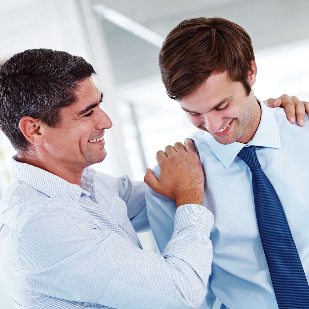 Man showing empathy with hands on male co-worker's shoulders