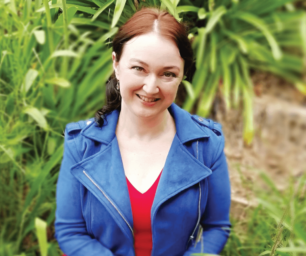 Jolene Stockman smiles in red shirt and blue jacket outside