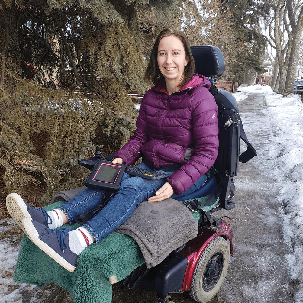 Girl in purple coat poses in wheelchair
