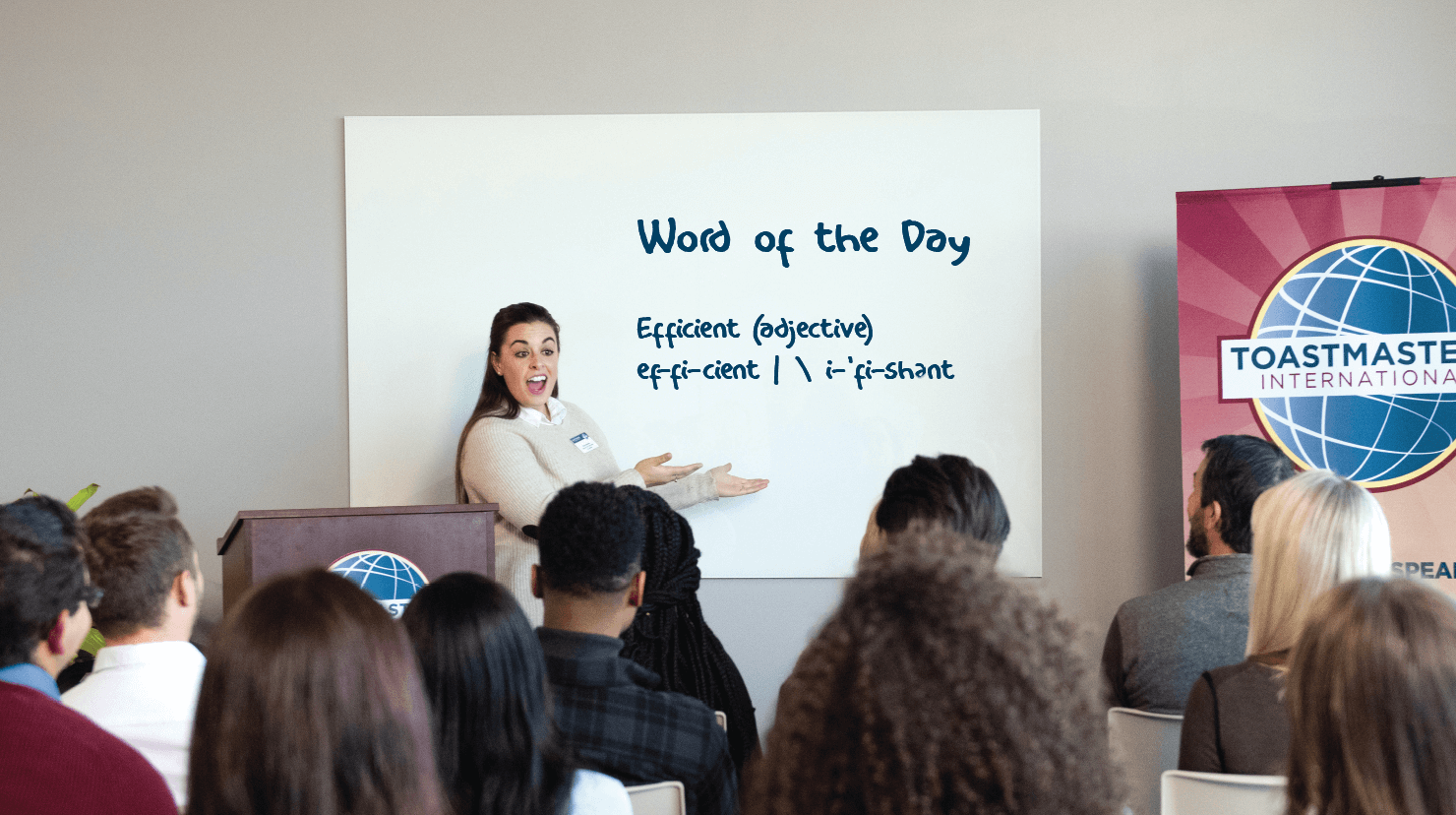 Woman stands in front of white board at Toastmasters meeting