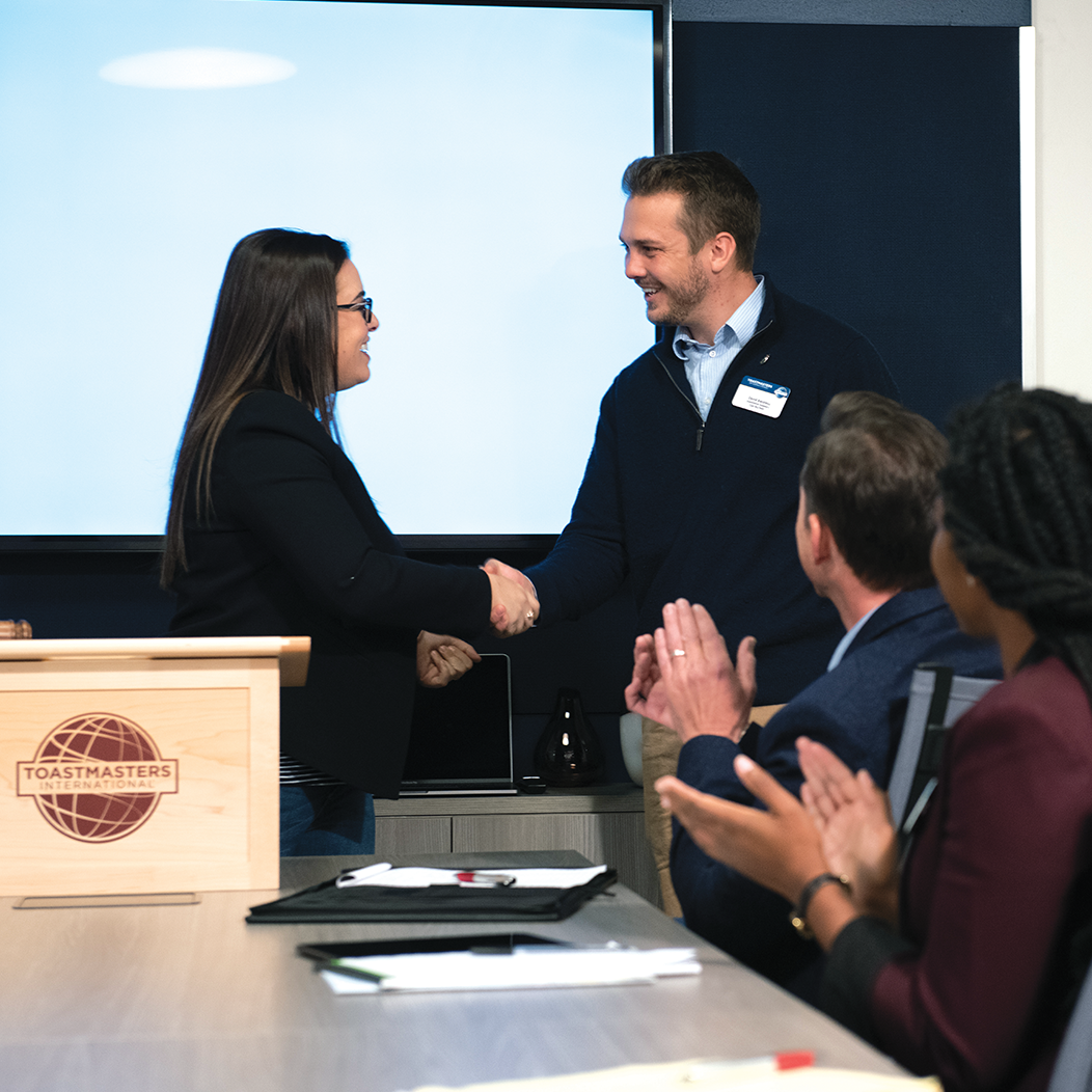 Woman at lectern shakes hands with man