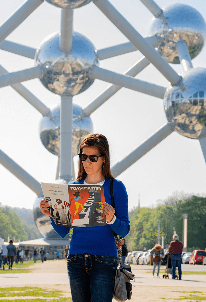 Agnes Inzsöl of Budapest, Hungary, keeps herself entertained while waiting to enter the Atomium in Brussels, Belgium. The Atomium was built for the 1958 Brussels World's Fair and is now a museum.