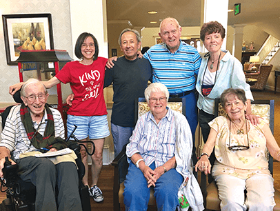 Senior citizens pose with Toastmasters volunteer
