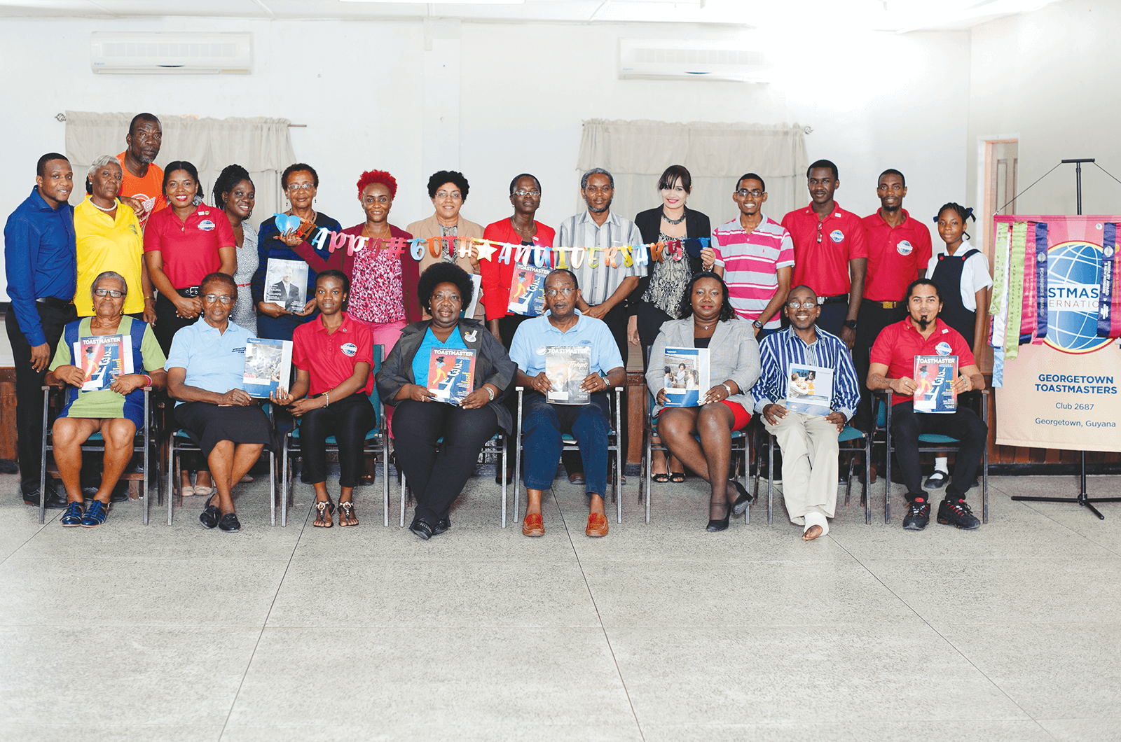 Group of Toastmasters members posing holding magazines
