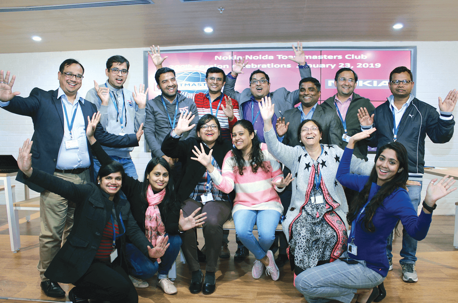 Group of Toastmasters members standing with banner