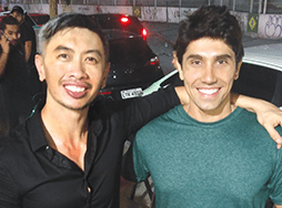Man in black shirt poses with man in green shirt