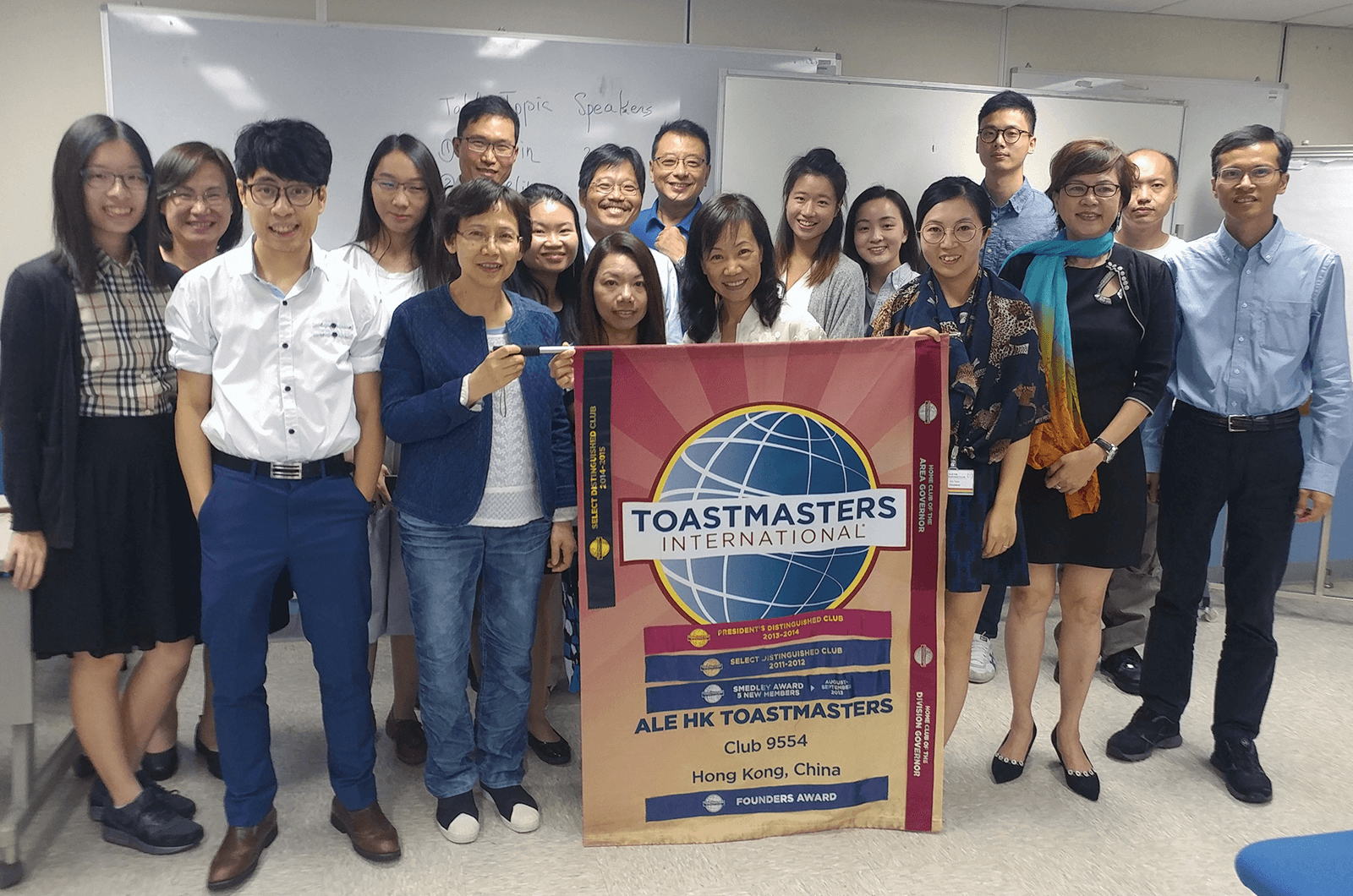 Group of Toastmasters members standing with club banner