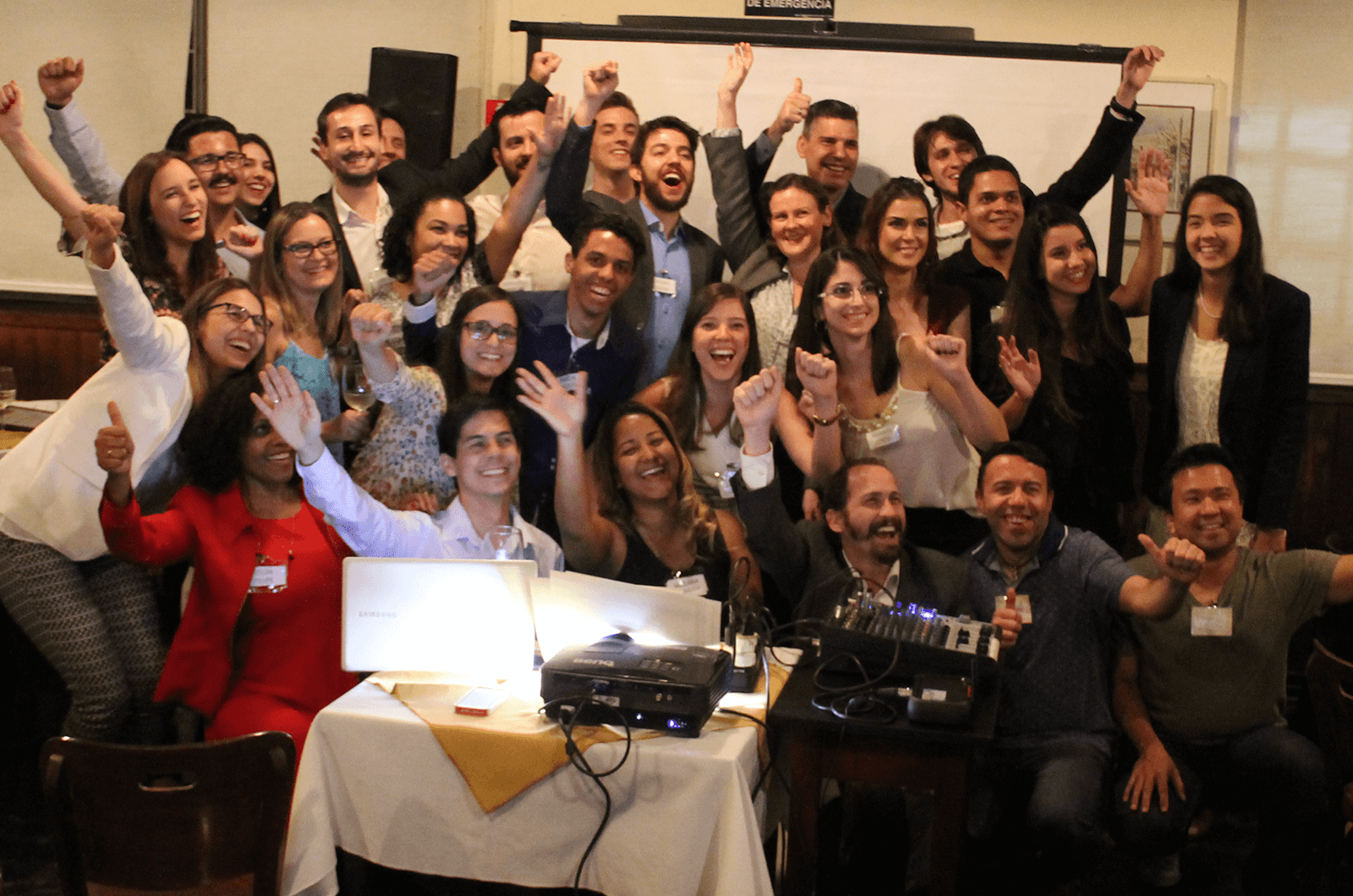 Group of Toastmasters posing with arms in the air