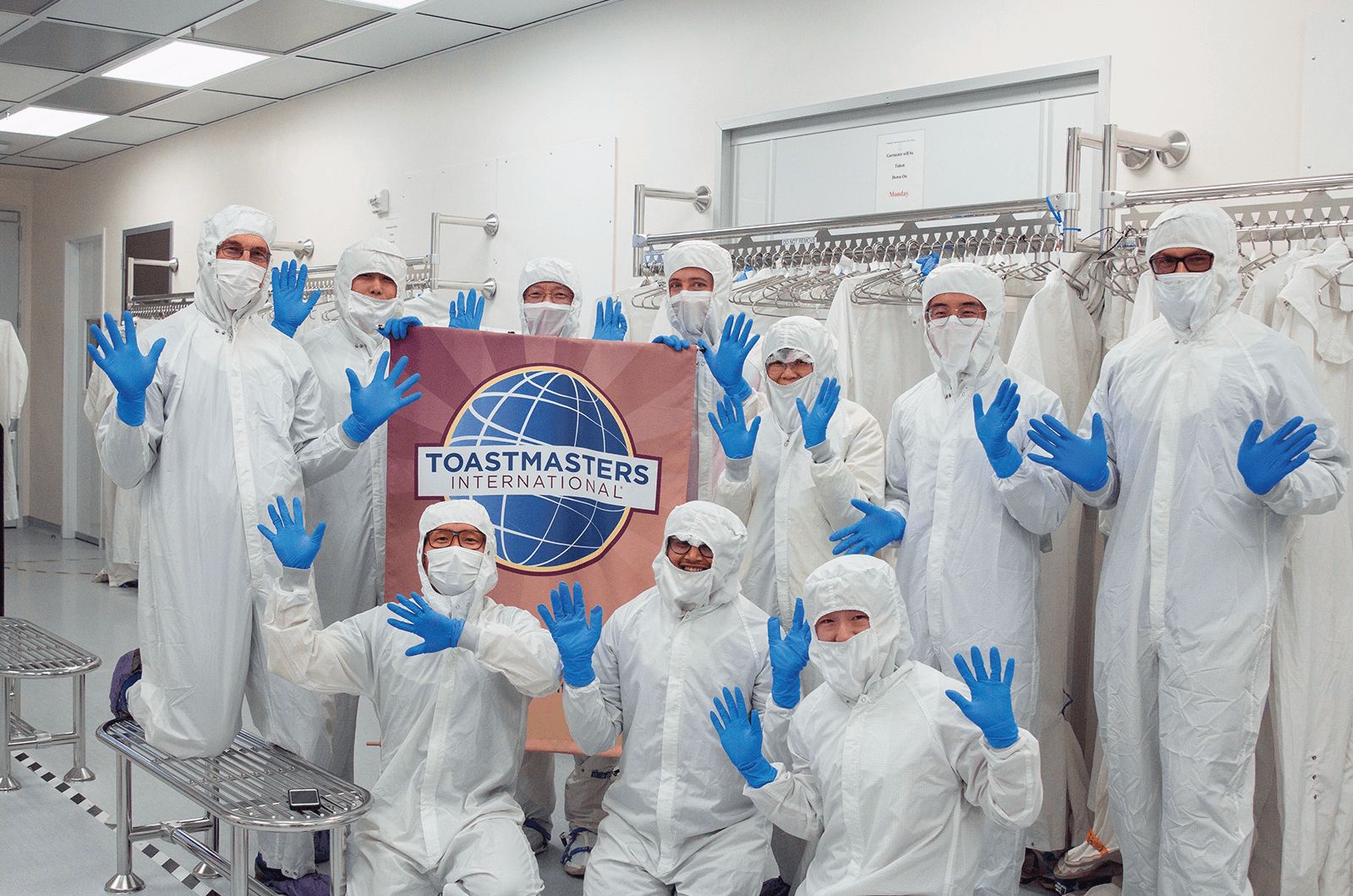 Group of Toastmasters dressed in white suits and blue masks in cleaning room