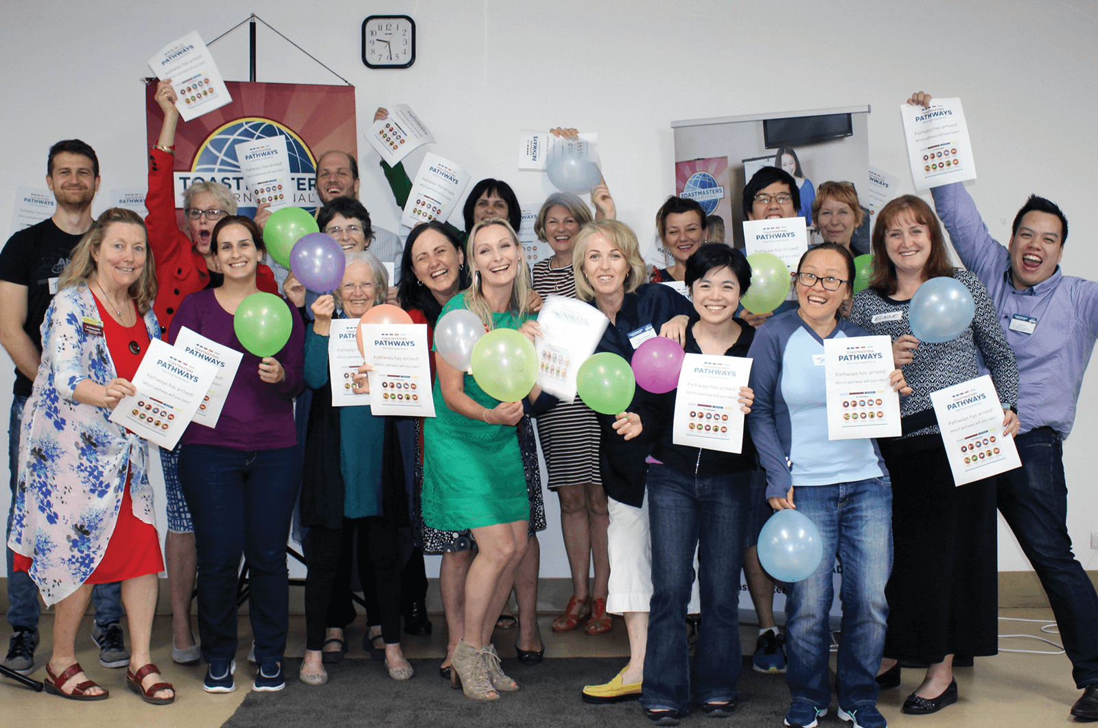 Group of Toastmasters members holding balloons and signs