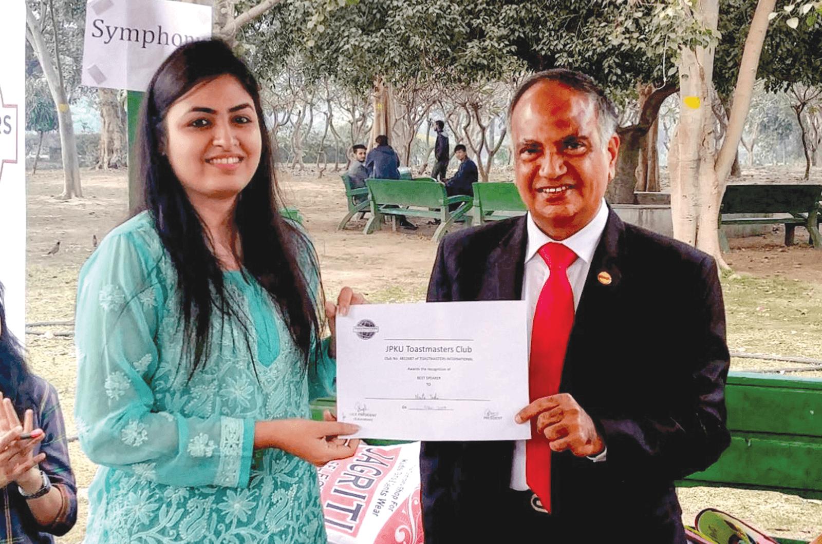 Menon awards a New Delhi JPKU club member the best speaker certificate.