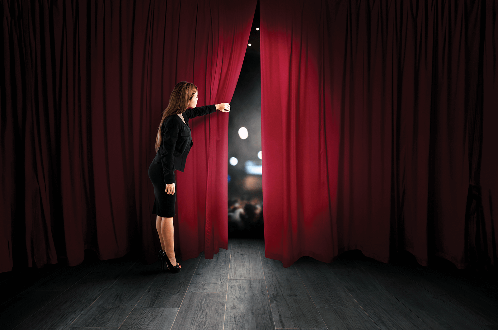 Woman peering from behind stage curtain